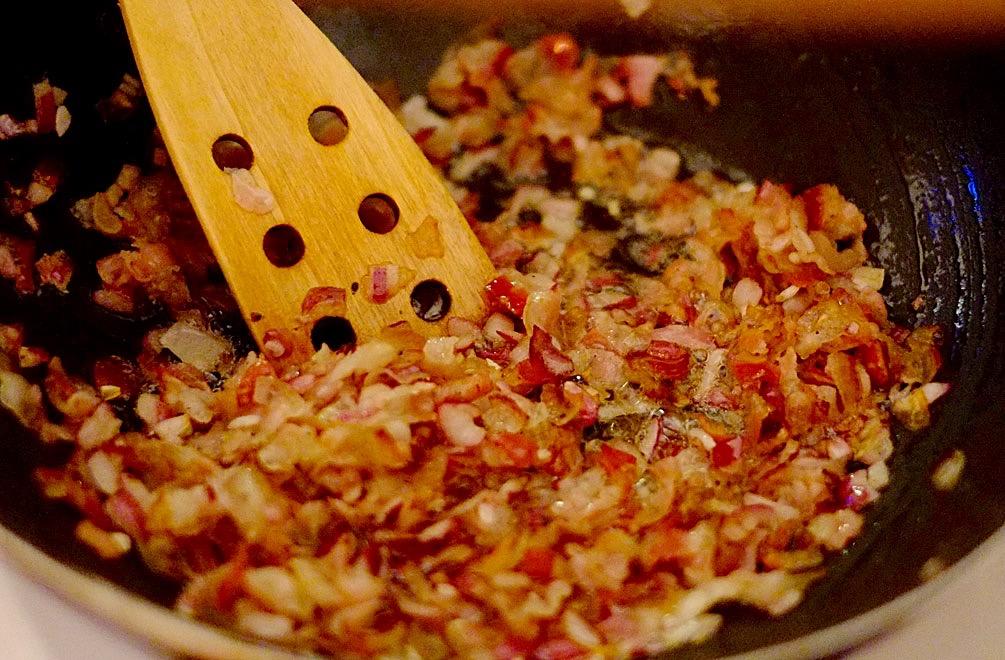 Zwiebeln und Pancetta in der Pfanne anbraten