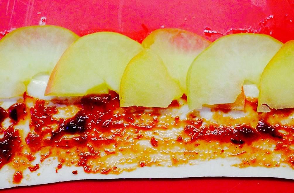 Die Teigstreifen werden mit Marmelade bestrichen und mit Äpfeln belegt